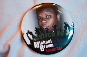 Foto La Jornada: Los residentes de Ferguson, donde fue abatido un adolescente negro por un policía, mandaron a hacer botones con la imagen del joven para exigir se investiguen las circunstancias de su muerte. Las manifestaciones se han tornado violentas, al grado que el fin de semana se ordenó un toque de quedaFoto Xinhua