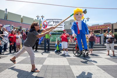 A woman hits the Donald Trump piñata during a rally at Mission and 16th streets against Donald Trump and his immigration remarks, Sunday, July 19, 2015, in San Francisco, California. Protesters marched along Mission Street and held a final demonstration at 24th Street.